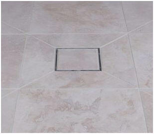 Square wet room floor gulley showing angled cuts in large ceramic tiles and a tile-in gully cover